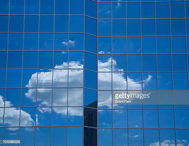 Single cloud reflected in office building