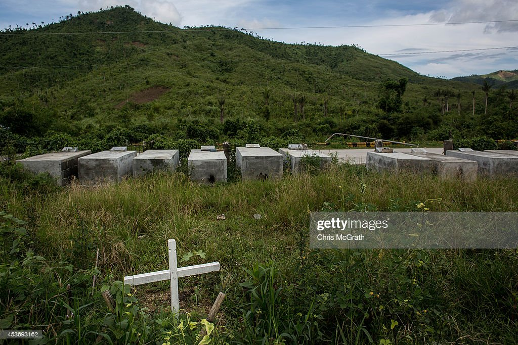 A single cross for Yolanda victims marks the site of the mass grave at Basber Public Cemetary on August 16, 2014 in Tacloban, Leyte, Philippines. Residents of Tacloban city and the surrounding areas continue to focus on rebuilding their lives nine months after Typhoon Haiyan struck the coast on November 8, 2013, leaving more than 6000 dead and many more homeless. With many businesses and government operations back up and running and with the recent start of the years typhoon season, permanent housing continues to be the main focus with many families still living in temporary accommodation. As well as continuing recovery efforts Leyte is preparing for the arrival of Pope Francis, who will visit the region from January 15- 19. on August 16, 2014 in Tacloban, Leyte, Philippines.
