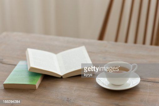 A single cup of tea on a wooden table with books : Stock Photo