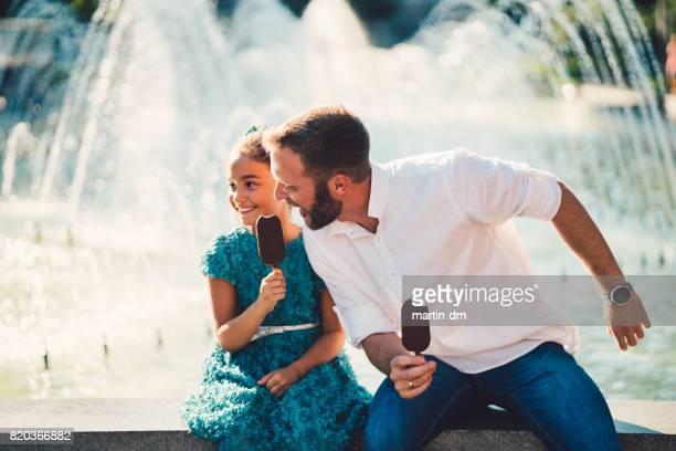 Solo padre e hija comer helado en la fuente