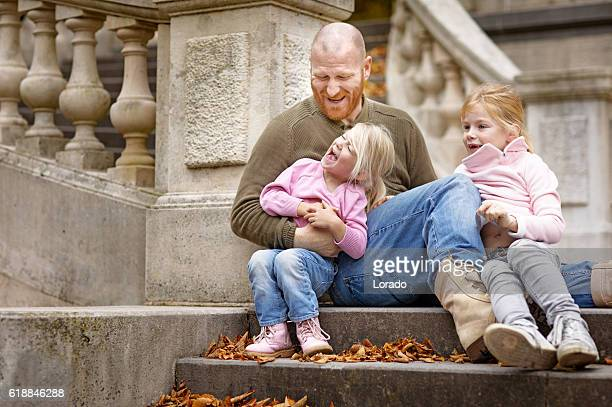 Single father and daughters laughing together on stately autumnal steps