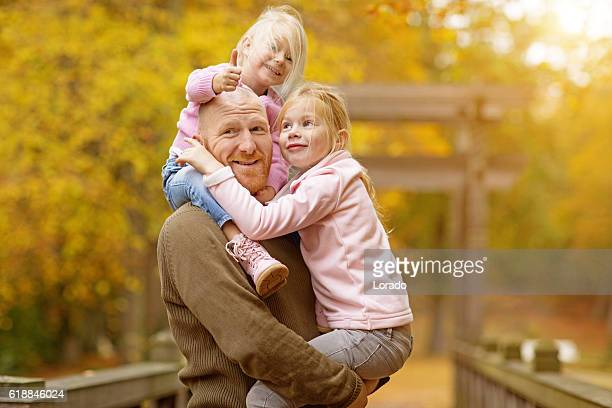 Single father and daughters posing together in autumnal park surroundings