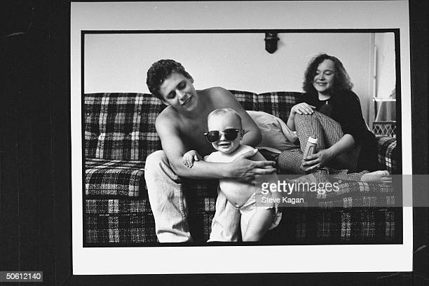 Single father Chad Sellers holding his 1yrold son Taylor who is wearing sunglasses as his girlfriend Cindy Wagner looks on while sitting on sofa in...