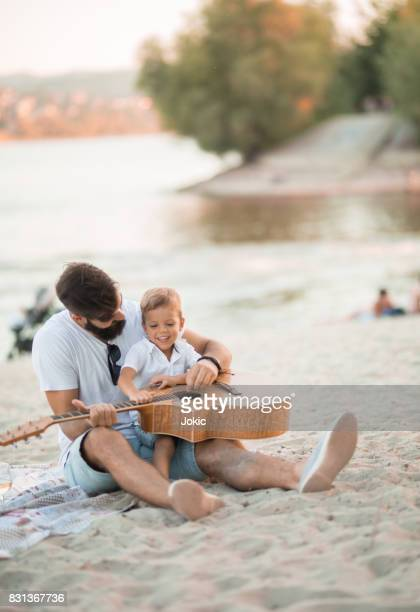 Single father is having fun at the beach with his son