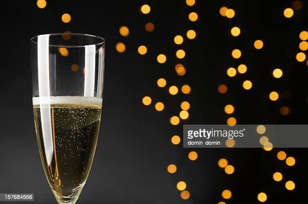 Single glass of Champagne, black background, defocused yellow, orange lights