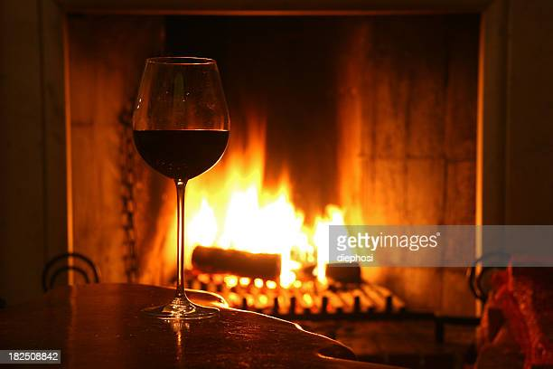 A single glass of wine by a fireplace