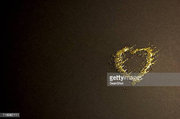 Single gold glittery heart over a black background