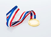 Single gold medal isolated on white background.
