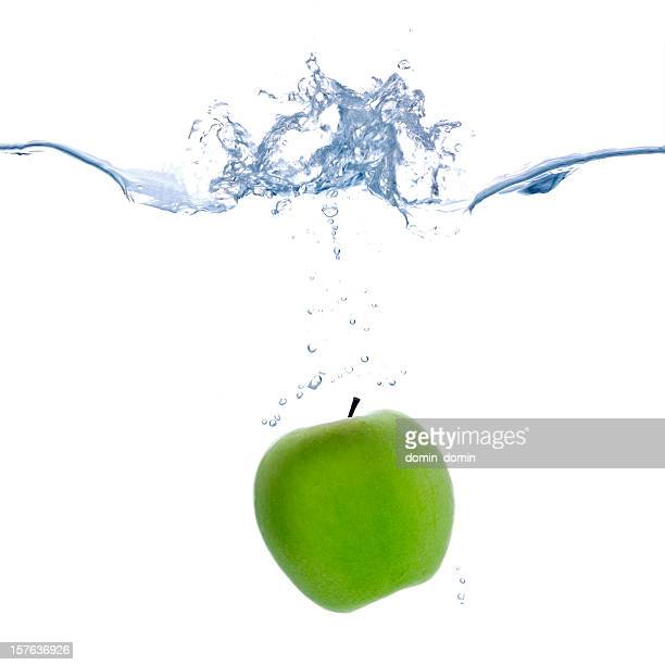 Single green apple falling into water, splashing, isolated on white