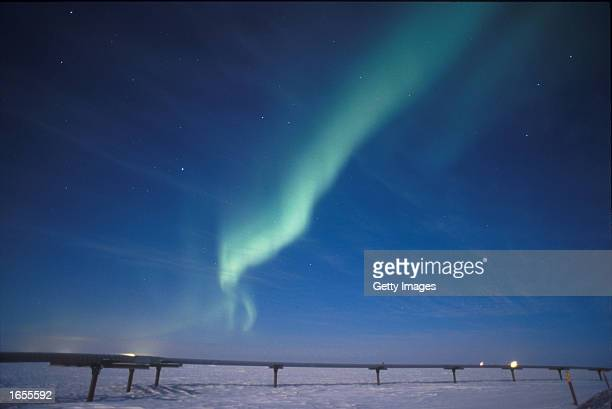 A single green arc of the Aurora Borealis stands out over the Alaska Pipeline under the illumination of a full moon November 19 2002 near Milne Point...