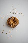 Single ground peanut coated on chocolate flour donut isolated on white background.