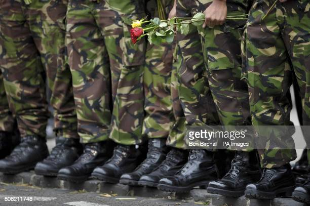 A single Gurkha soldier holds red and yellow roses as they wait for the Union Flag draped coffins containing the bodies of Sapper Darren Foster of 21...