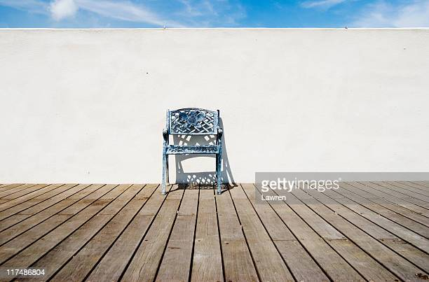 Single iron chair in front of white wall