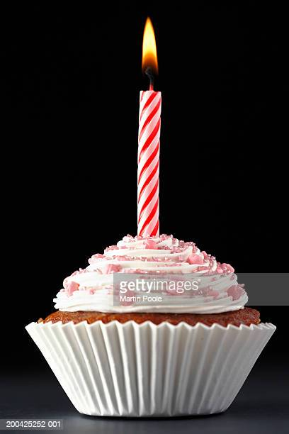Single lit candle on iced cup cake, close-up