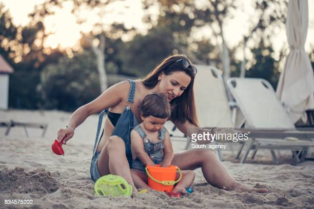 Single mother and baby daughter playing at the beach