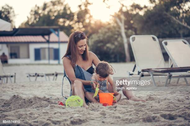 Single mother and daughter playing at the beach