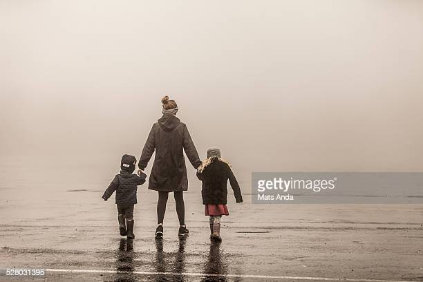 Single mother and two kids walking into fog