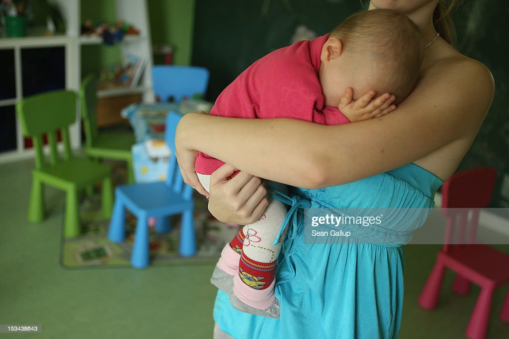 Single mother Nancy Kett, 19, cradles her 11-month-old daughter Lucy in the playroom of the 'Jule' facility for single parents in Marzahn-Hellersdorf district on October 5, 2012 in Berlin, Germany. The Jule project helps single parents by helping them to find jobs, job training and housing, advice on child development and day care in Marzahn-Hellersdorf, a district in east Berlin with high levels of unemployment and social problems. Currently 14 single mothers and one single father are participaring at Jule, which opened its doors in the spring of 2012.