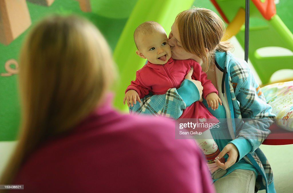 Single mother Nancy Kett, 19, kisses her 11-month-old daughter Lucy in the playroom of the 'Jule' facility for single parents in Marzahn-Hellersdorf district on October 5, 2012 in Berlin, Germany. The Jule project helps single parents by helping them to find jobs, job training and housing, advice on child development and day care in Marzahn-Hellersdorf, a district in east Berlin with high levels of unemployment and social problems. Currently 14 single mothers and one single father are participaring at Jule, which opened its doors in the spring of 2012.