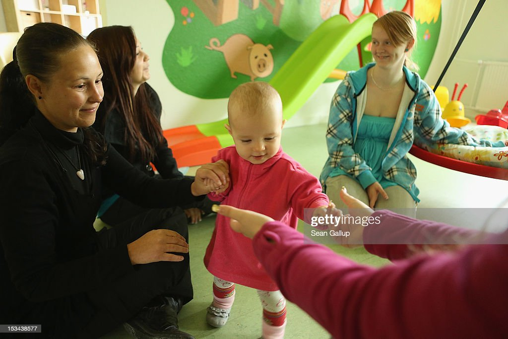 Single mother Nancy Kett (R), 19, watches as volunteers, including Anja Goeckeritz (L) and Anni Wiedermann, play with her 11-month-old daughter Lucy in the playroom of the 'Jule' facility for single parents in Marzahn-Hellersdorf district on October 5, 2012 in Berlin, Germany. The Jule project helps single parents by helping them to find jobs, job training and housing, advice on child development and day care in Marzahn-Hellersdorf, a district in east Berlin with high levels of unemployment and social problems. Currently 14 single mothers and one single father are participaring at Jule, which opened its doors in the spring of 2012.