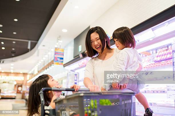 Single mother with two kids shopping in a supermarket