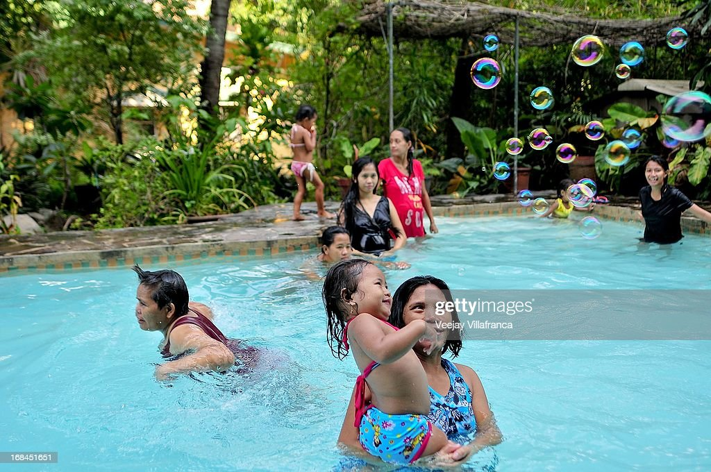 Single mothers coming from different provinces in the Philippines play in a swimming pool at Nazareth House, before Mother's Day this Sunday, on May 10, 2013 in Manila, Philippines. The Nazareth home take in women who are expecting mothers and have no capacity to raise a child due to varied socio-economic reasons. Women in the center usually have suffered mental or sexual abuse and undergo a series of counseling and are also provided maternal health support by the volunteers.