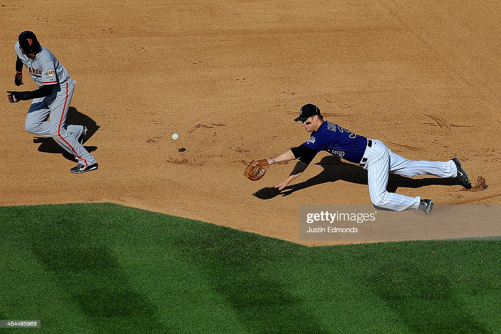 A single off the bat of Brandon Crawford (not pictured) of the San Francisco Giants sneaks past first baseman <a gi-track='captionPersonalityLinkClicked' href=/galleries/search?phrase=Justin+Morneau&family=editorial&specificpeople=211556 ng-click='$event.stopPropagation()'>Justin Morneau</a> #33 of the Colorado Rockies as Joaquin Arias #13 avoids the ball on his way to advancing to third base during the fourth inning at Coors Field on September 1, 2014 in Denver, Colorado. The Rockies defeated the Giants 10-9 on a walk-off single by Charlie Blackmon.