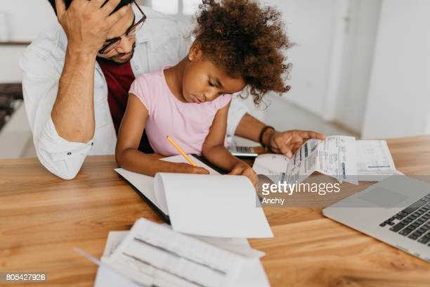 Single parent doing finances at home with his daughter