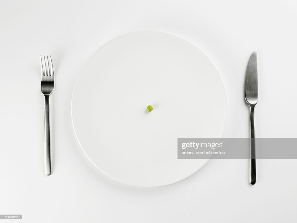 Single pea on white plate (close-up, directly above) : Stock Photo