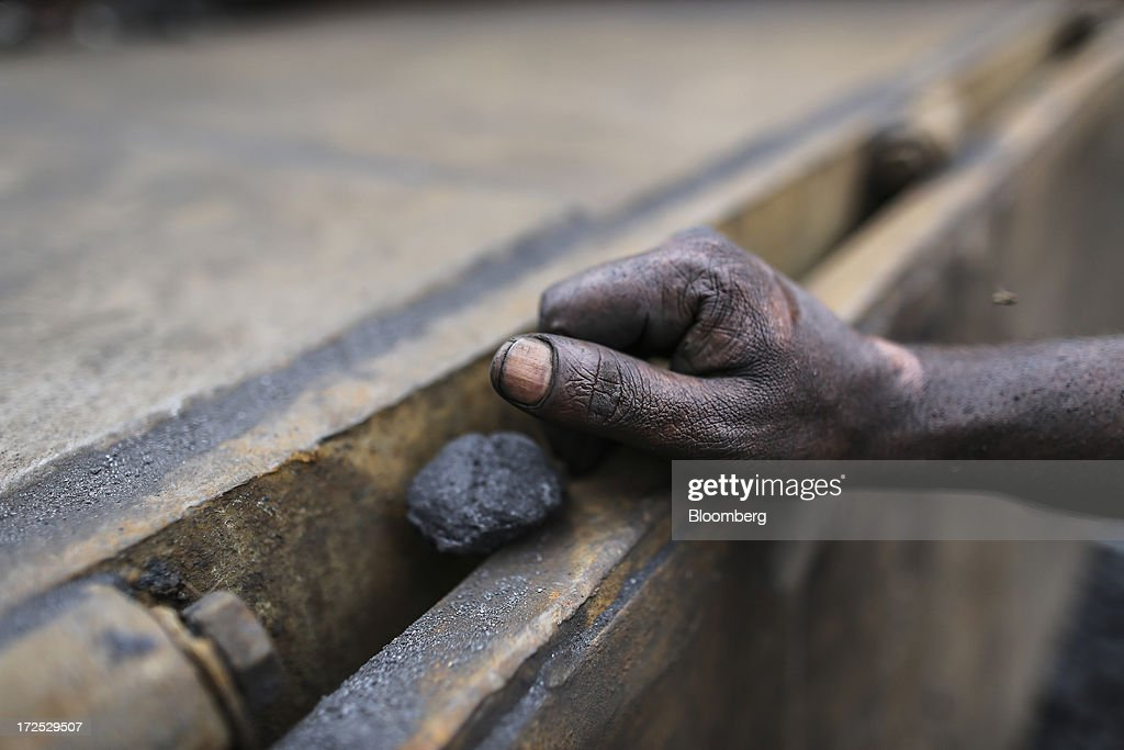 A single piece of coal sits by a worker's hand as he waits during the unloading of a truck at a coal wholesale market in Mumbai, India, on Tuesday, July 2, 2013. India, the worlds third-largest coal consumer, imported 43 percent more of the fuel than a year ago on increased demand from power stations and steelmakers, according to shipping data, and is set to eclipse China as the top importer of power station coal by 2014. Photographer: Dhiraj Singh/Bloomberg via Getty Images