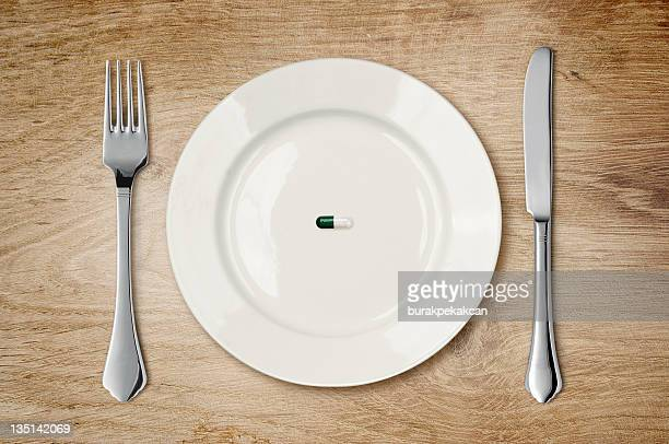 Single pill on an empty plate with knife and fork