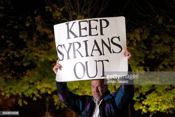 A single protester displays a placard demanding to keep out Syrians as Human rights activists and people from the Muslim community demonstrate in New...
