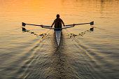 Single female rower in sunrise