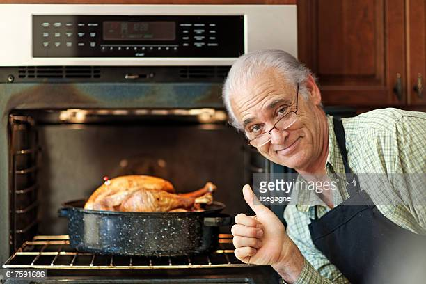 Single senior man cooking turkey