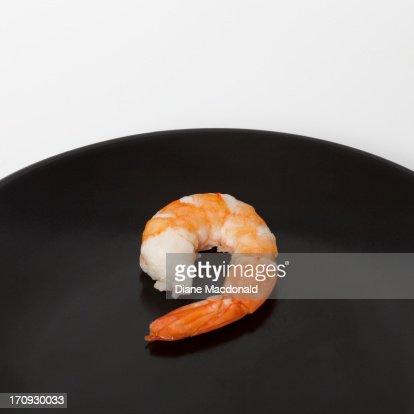 A single shrimp on a black plate : Stock Photo