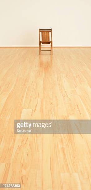 Single Small Chair at End of Long, Empty Room