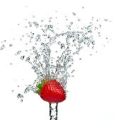 A single strawberry with a splash of water