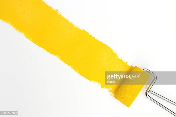 Single streak of yellow paint with rollers over white