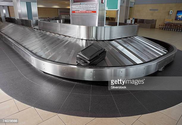 Single suitcase on airport baggage claim carousel