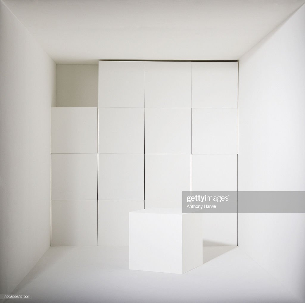 Single white cube missing from wall of cubes