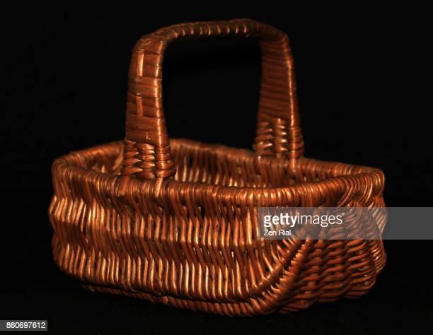 A single wicker basket on black background
