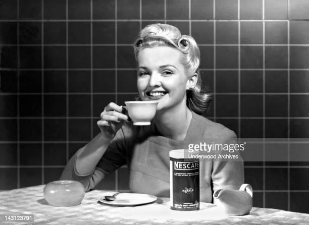 A single woman at a kitchen table enjoys a cup of Nescafe circa 1960