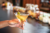 Single woman drinking dry martini alone in a bar