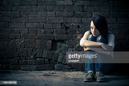 Single woman holding her knees on the street : Stock Photo