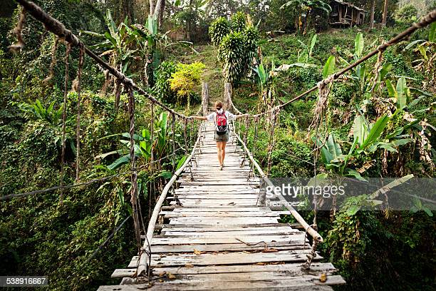 Single woman with backpack on suspension bridge in rainforest