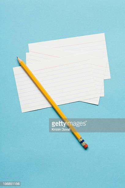 Single yellow sharpened pencil with blank note cards