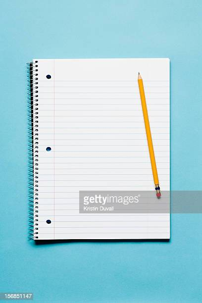 Single yellow sharpened pencil with blank spiral notebook on blue background