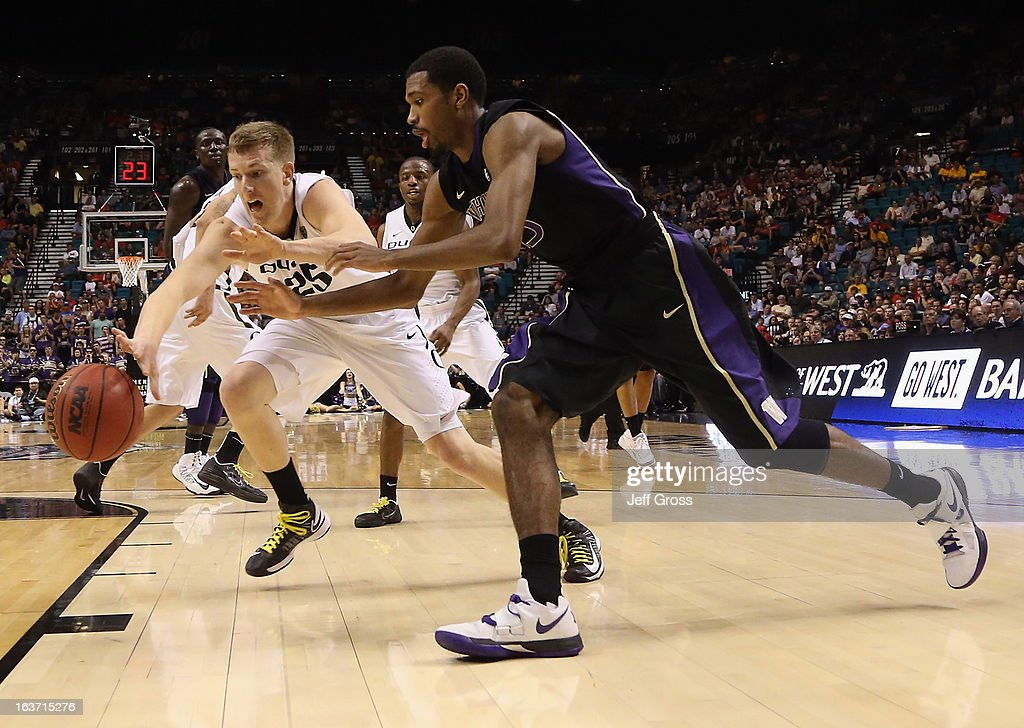 E.J. Singler #25 of the Oregon Ducks and Scott Suggs #15 of the Washington Huskies fight for a loose ball in the first half during the quarterfinals of the Pac 12 Basketball Tournament at the MGM Grand Garden Arena on March 14, 2013 in Las Vegas, Nevada.