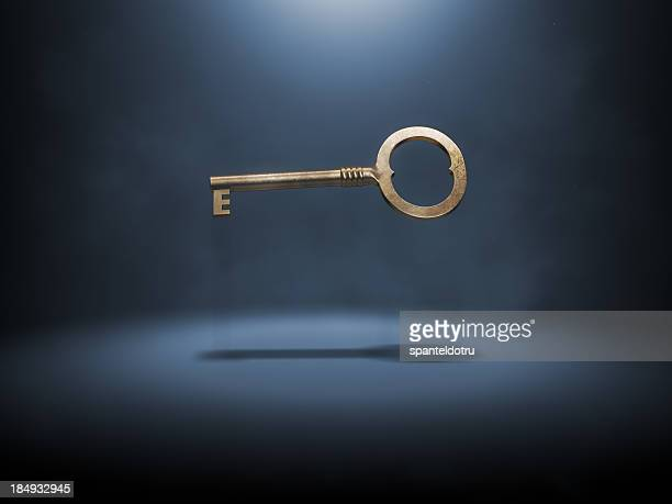 A singular gold key suspended in the air