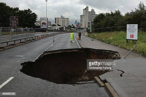 A sink hole appears on Mancunian Way in Manchester after heavy rain on August 14 2015 in Manchester England Heavy rain and flood warnings have been...